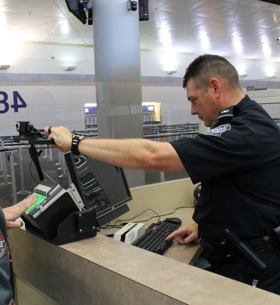 A CBP officer at DFW airport processes an arriving traveler.