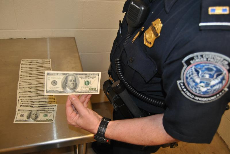 A CBP officer holds one of 37 counterfeit $100 bills seized at DFW on Monday