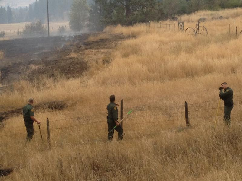 U.S. Border Patrol agents putting out fires on the edge of property