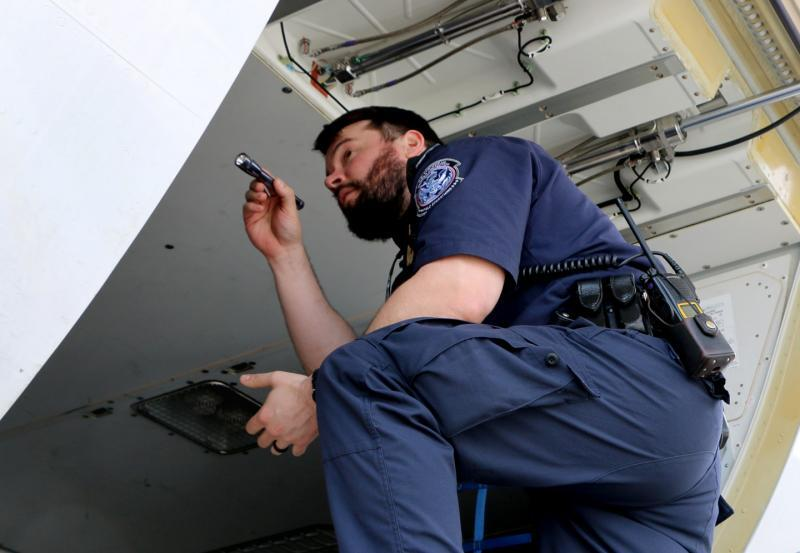 A CBP officer inspects the cargo hold of an airplane that arrived at Washington Dulles International Airport from a foreign location.