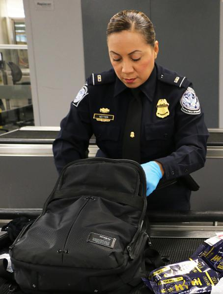 CBP officer inspecting a traveler's backpack.