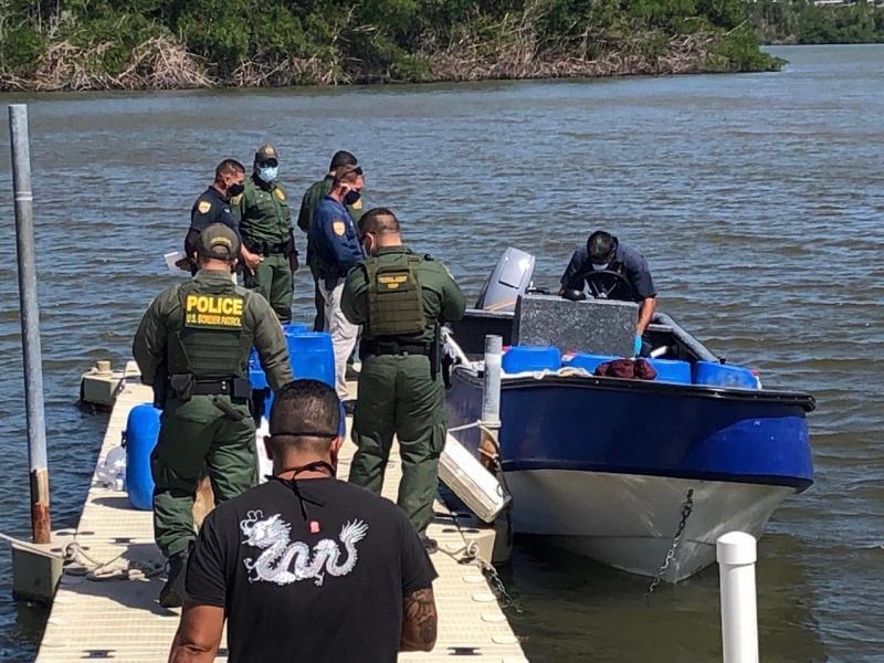 Border Patrol agents and PRPD Officers inspect the yola vessel after it was found hidden within mangroves. .