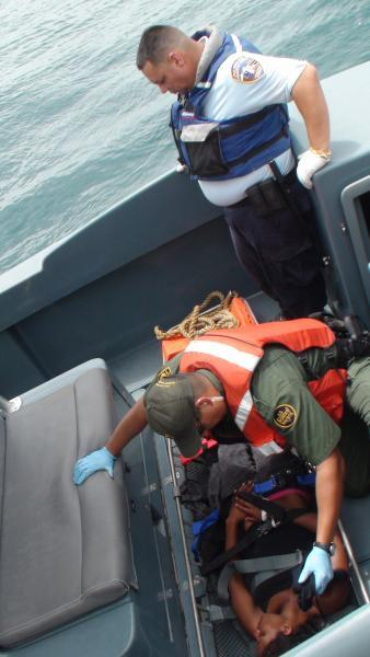 A Border Patrol Agent and a FURA Officer assist a migrant at sea.