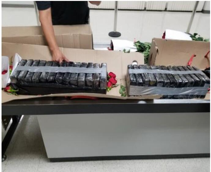 On display the opened boxes exposing the 26 bricks of cocaine with roses around.
