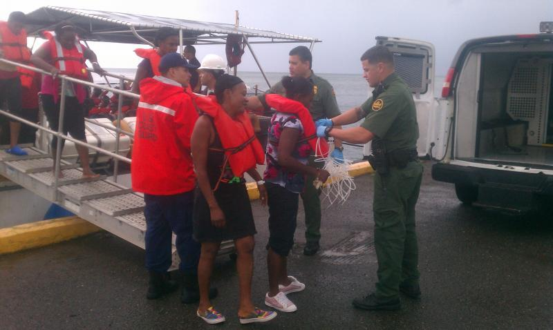Migrants leave a US Coast Guard cutter into the custody of Ramey Sector Border Patrol Agents in Mayaguez