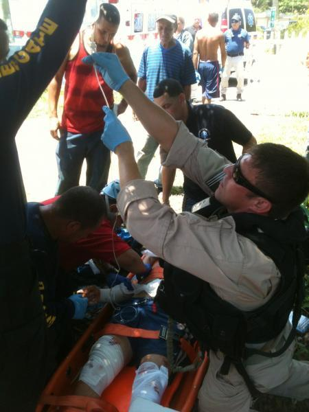 A CBP EMT administers an an intravenous serum to the injured swimmer.