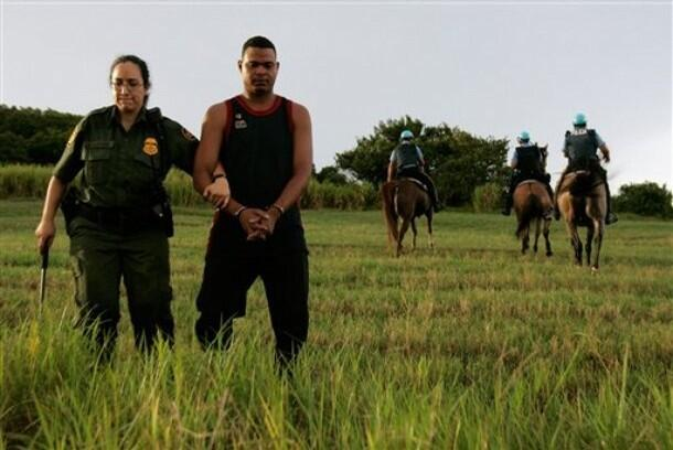 Photo of Border Patrol agent with a handcuffed suspect