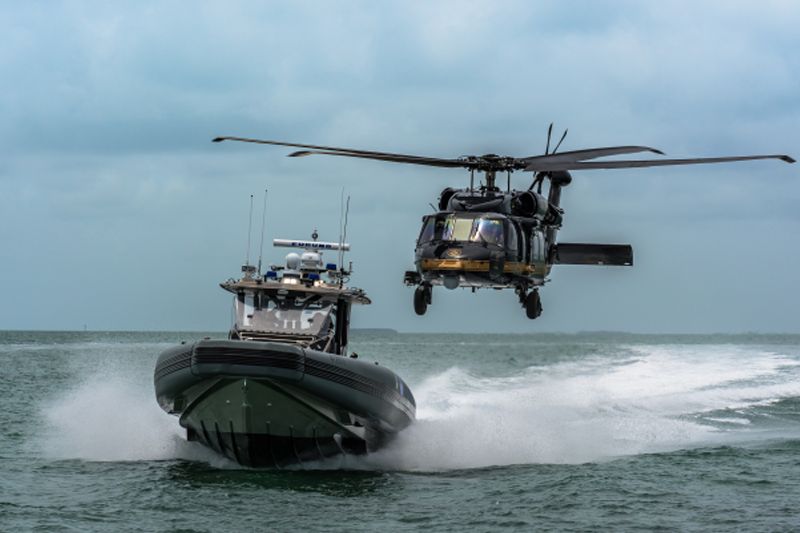 Air and Marine operations boat in the water with Air and Marine helicopter traveling right behind.