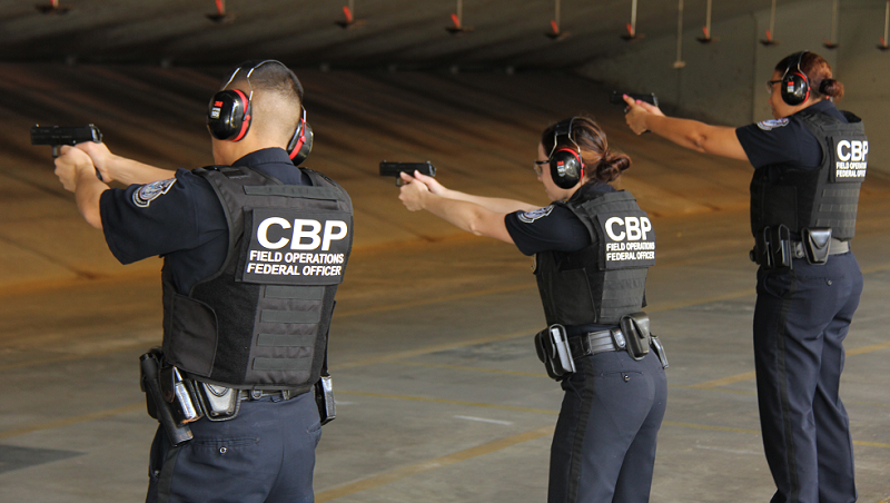 Three CBP Officer Trainees, holding firearms, practicing how to apply basic tactical concepts and methodologies to resolve a variety of use of force scenarios.