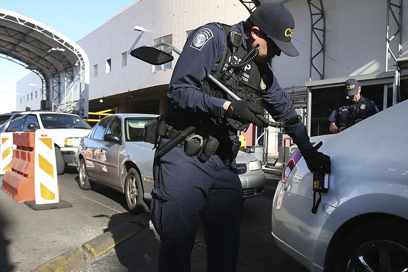 CBP Officer using device on vehicle.