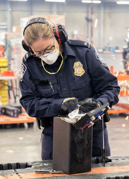 A U.S. Customs and Border Protection Officer inspects a metal box containing conceled meth