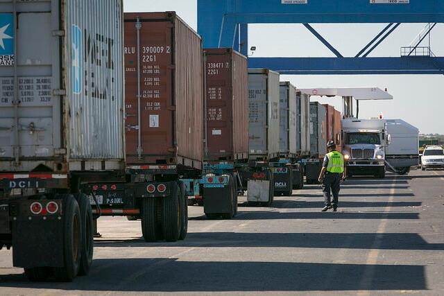 A CBP officer inspects a truck of cargo.