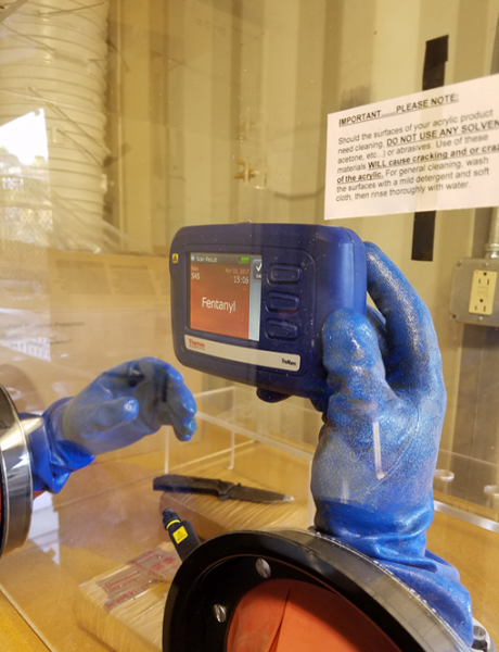 One of many devices used in the field to detect contraband, this TruNarc substance analyzer identifies multiple types of narcotics. The gloved manipulators protect officers while testing for drugs. Photo courtesy of CBP NTC