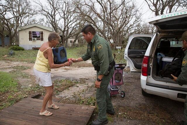 U.S Border Patrol agent Mario Fuentes rolls the belonging of a disaster survivor to a bus to evacuate her and her dog Chester in the wake of Hurricane Harvey.