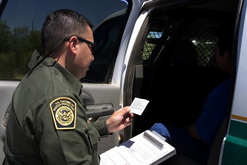 Border Patrol agent inspects identification document