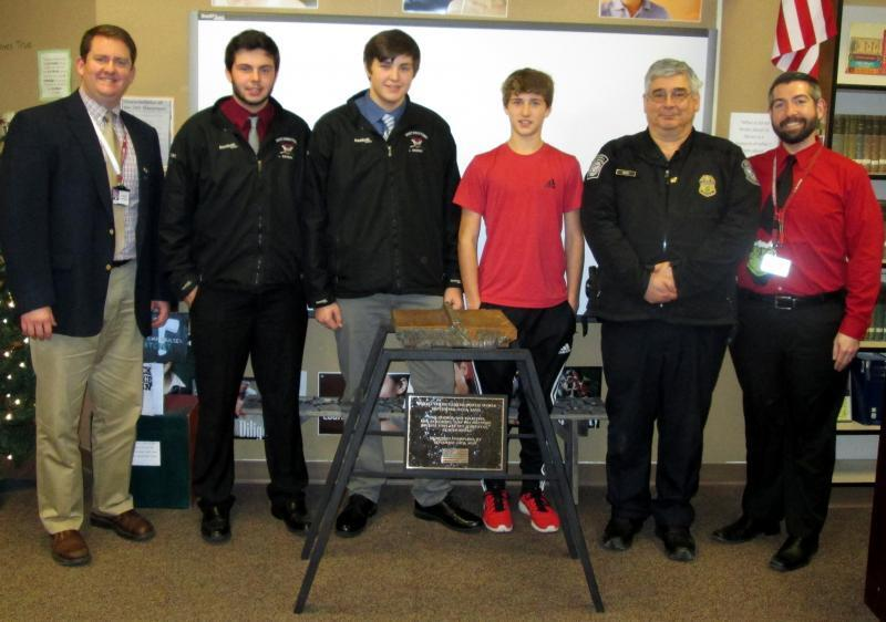 School students and officials pose with 9/11 artifact on loan from CBP Champlain