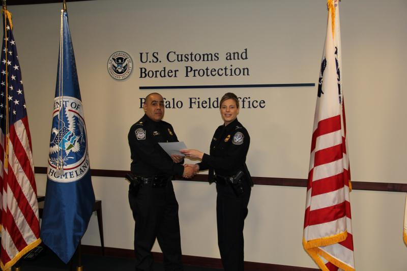 Customs and Border Protection Acting Director of Field Operations, Rose Hilmey (right), presents Supervisory CBP Officer Jose Lorenzo (left) with the CBP Commissioner's Humanitarian Award.