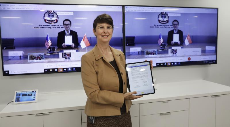 CBP Executive Assistant Commissioner Brenda Smith displays the signed letter of intent while Singapore Customs Deputy Director General Lim Teck Leong appears onscreen behind her.