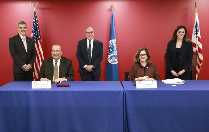 Photo of CBP Executive Assistant Commissioner William Ferrara and U.S. Chamber of Commerce President and CEO Suzanne Clark signing the MOU as senior CBP and U.S. Chamber officials look on.
