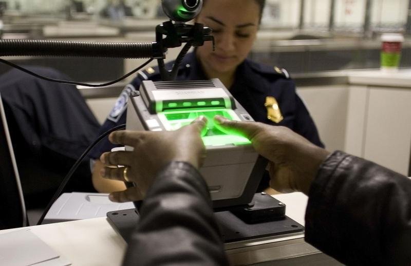A Customs and Border Protection officers uses a fingerprint scanner.