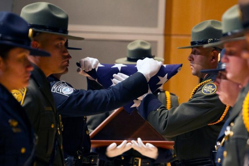 Members of the Border Patrol, Air and Marine Operations and Field Operations Honor Guards prepare a memorial flag to be encased in a display box May 13 during the Valor Memorial and Wreath Laying Ceremony at the Ronald Reagan Building amphitheater in Washington, D.C. The annual ceremony honors the agents and officers of CBP and its legacy agencies who died in the line of duty. Photo Credit: Donna Burton